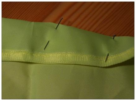Sedan viker du upp nederkanten på reflexvästen mot avigsidan några cm och syr med raksöm. Sätt en säkerhetsnål i varje ände på resårbandet och trä i kanalen.